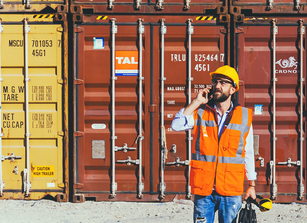 Supply chain professional next to shipping containers