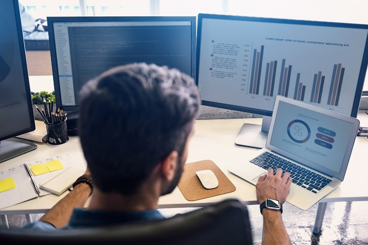 Analytics professional working on two desktop monitors