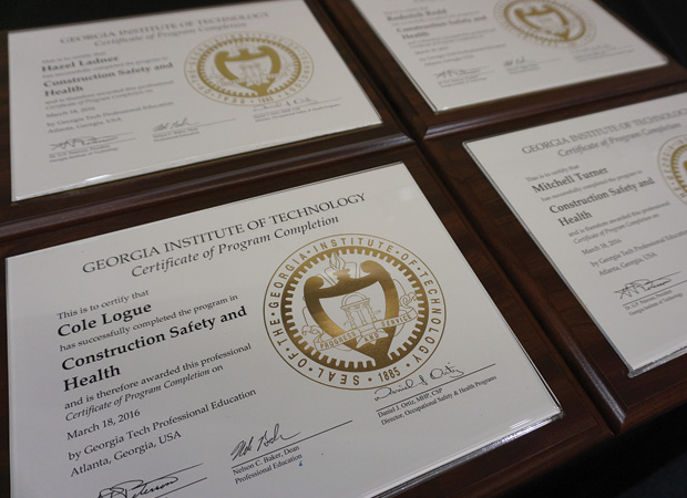Picture of four diplomas laid out on table