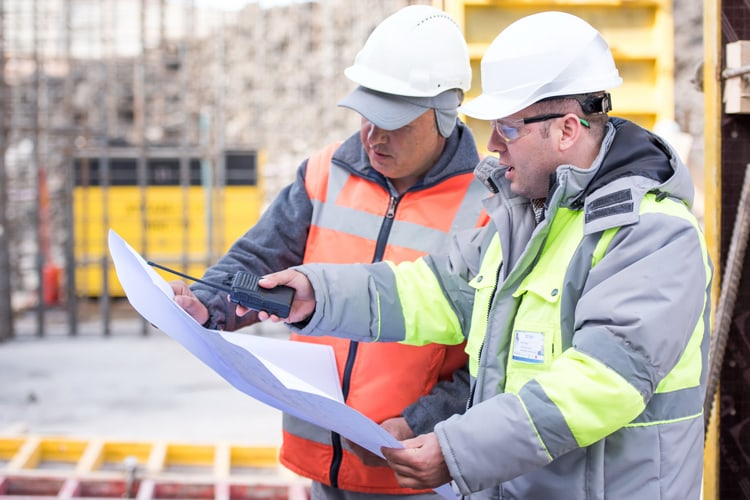 Civil engineers reviewing construction plans on job site