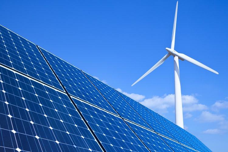 A  wind turbine producing energy alongside solar panel
