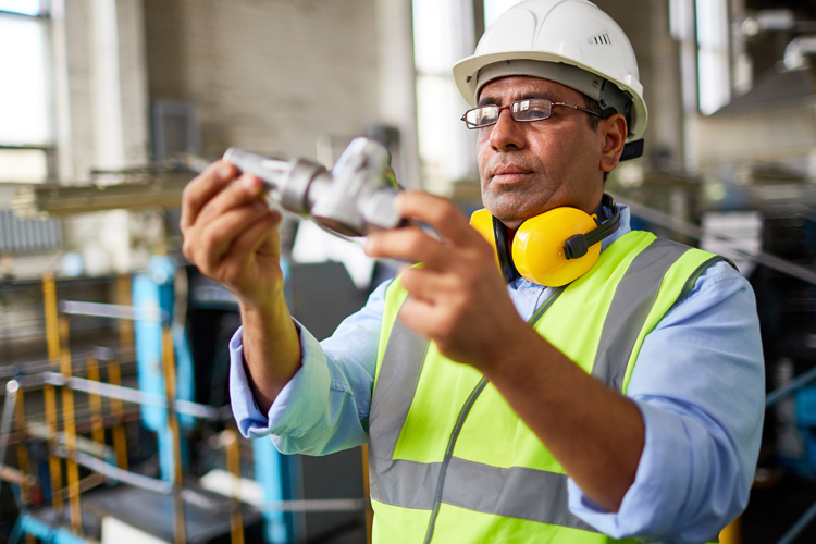 Manufacturing professional in safety gear inspecting a part