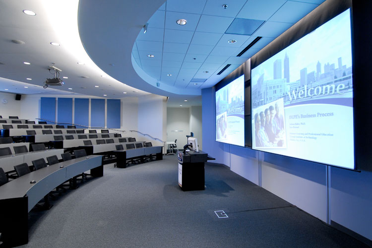 Empty amphitheater with presentation displayed on two projector screens