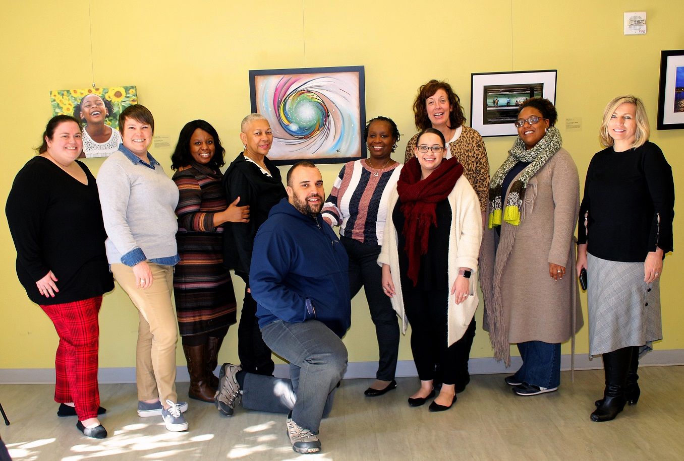 GTPE staff gather around Lewis' artwork at the artists' reception.