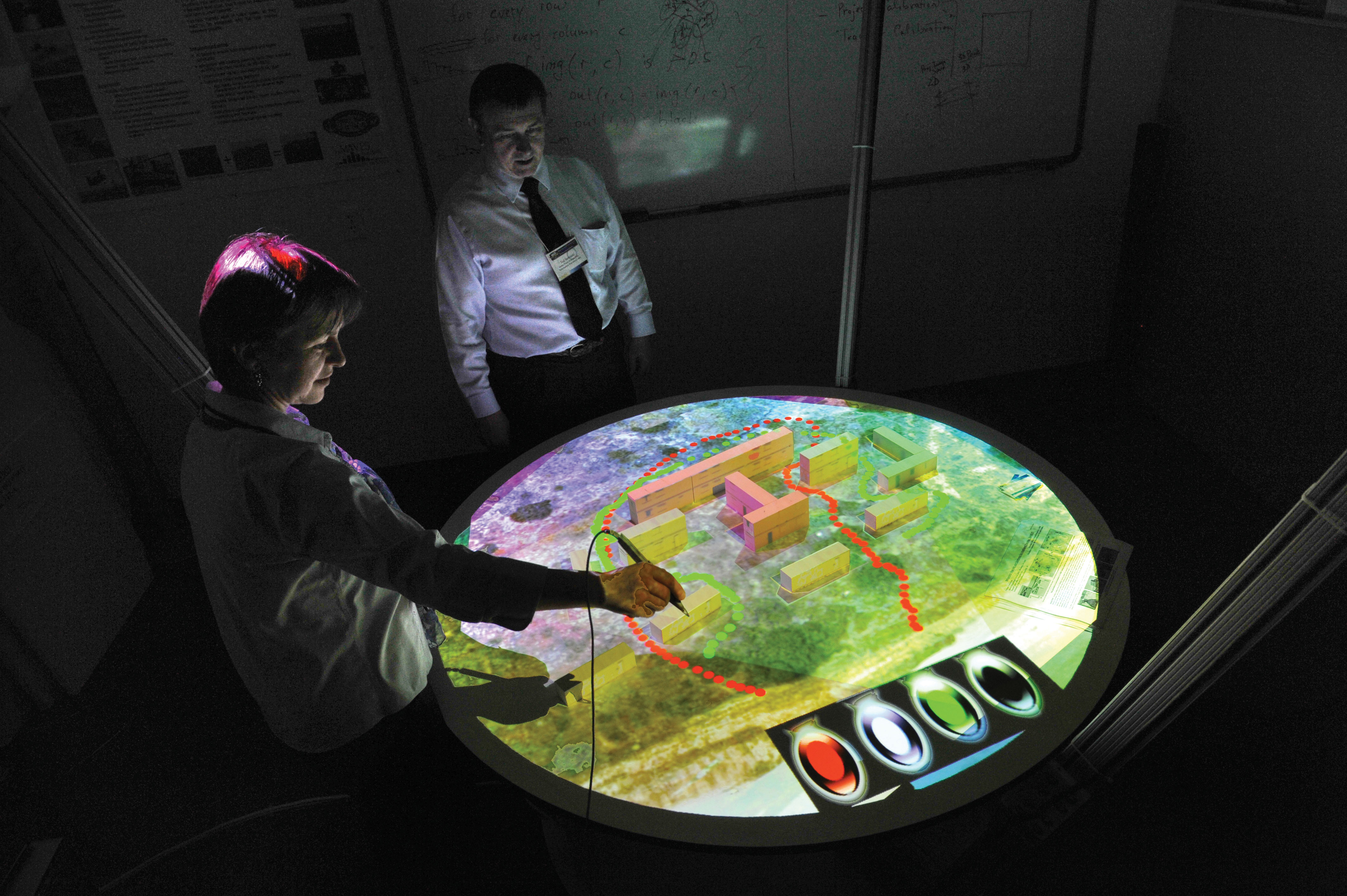 Two individuals using touchscreen technology