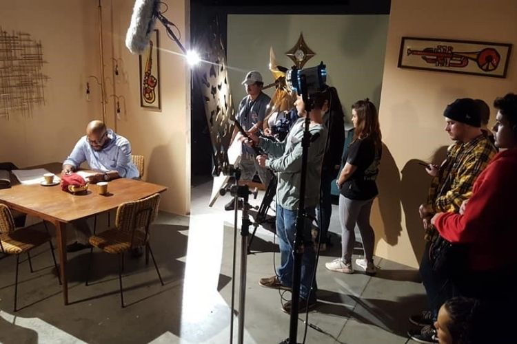 Group of film studios record actor sitting a kitchen table