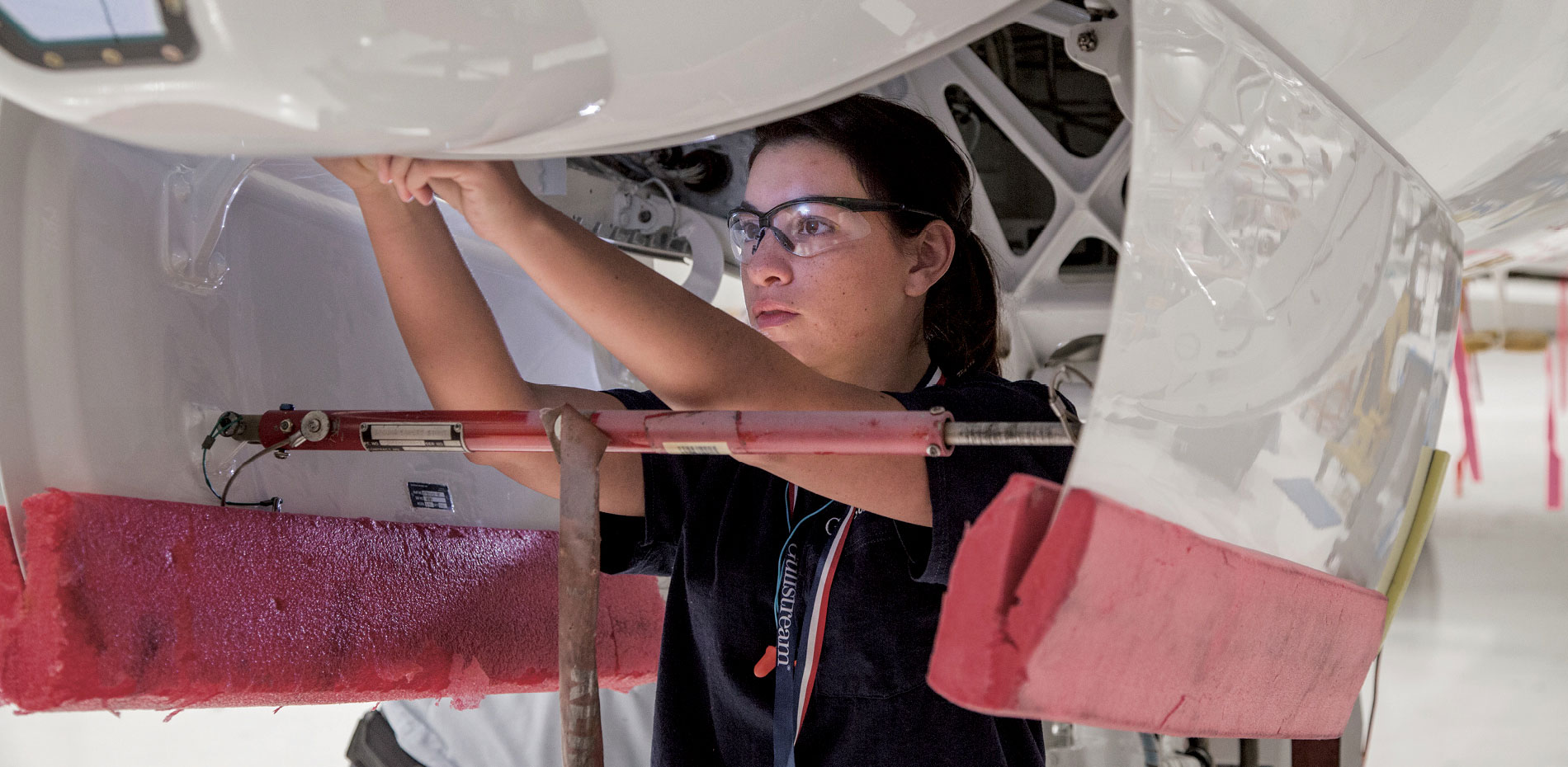 Spc. Victoria Frizalone adjusts the latches of the nosecone of a G450 at the Service Center of Gulfstream Aerospace.