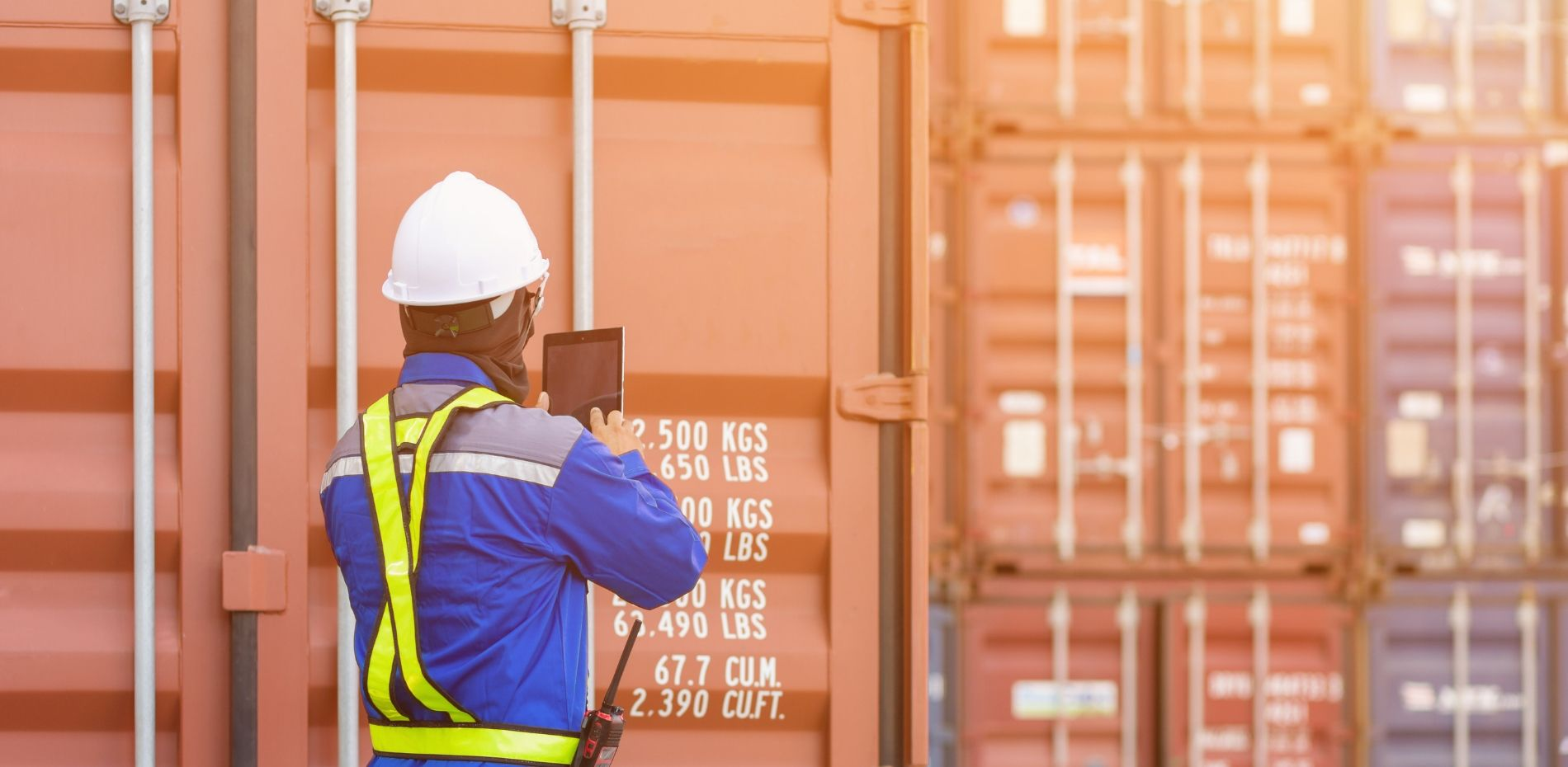 Port docker wearing hard hat and safety vest, standing in front of freight containers looking at supply chain trends on tablet