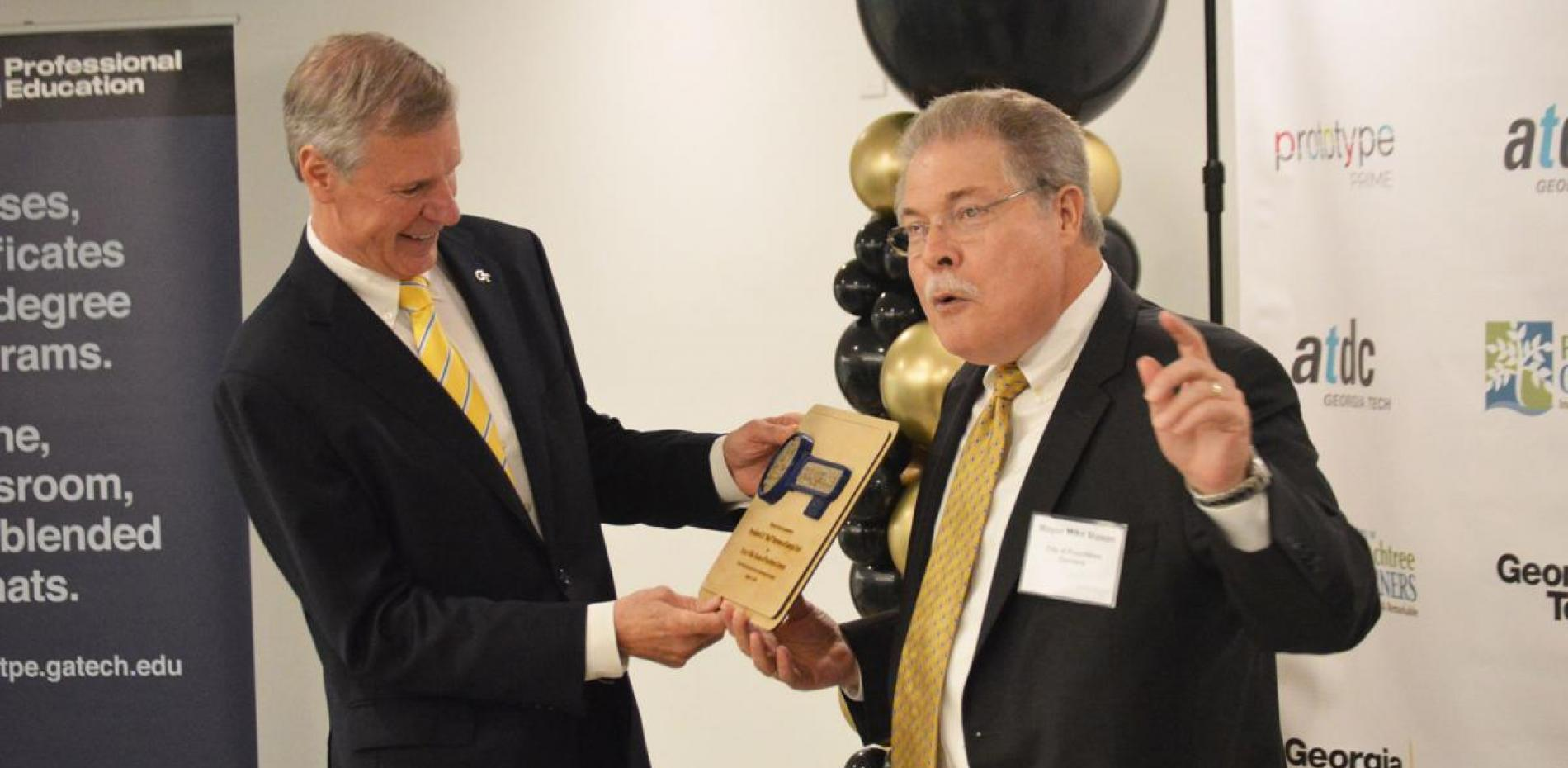 Georgia Tech president Bud Peterson presented key to Peachtree Corners by mayor Mike Mason