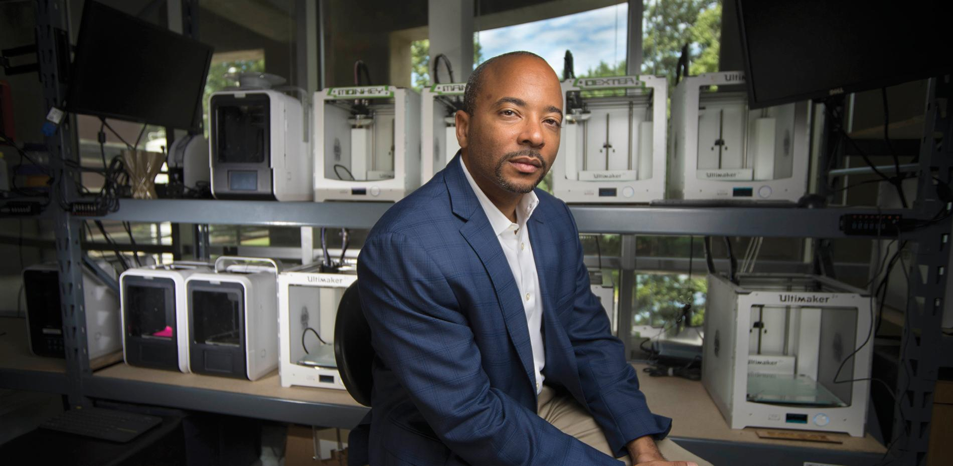 Raheem Beyah looking at camera thoughtfully as he sits in an additive manufacturing lab at Georgia Tech