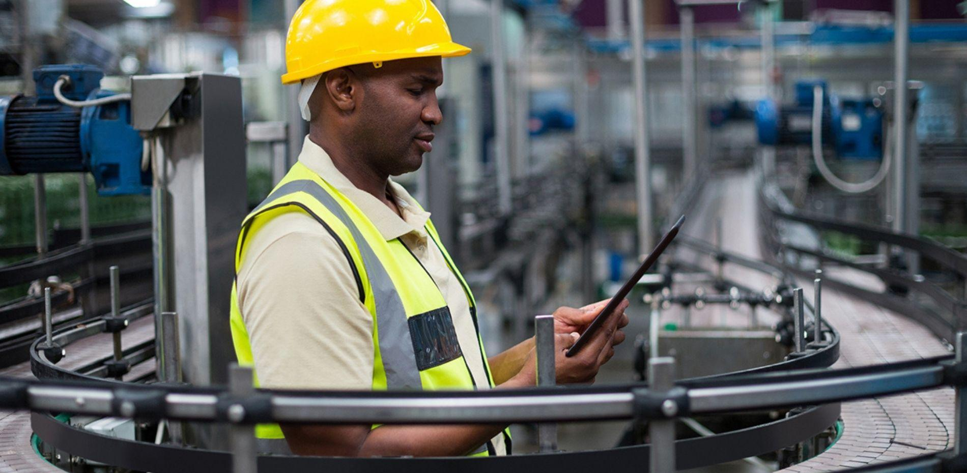 Manufacturing professional working on tablet in factory