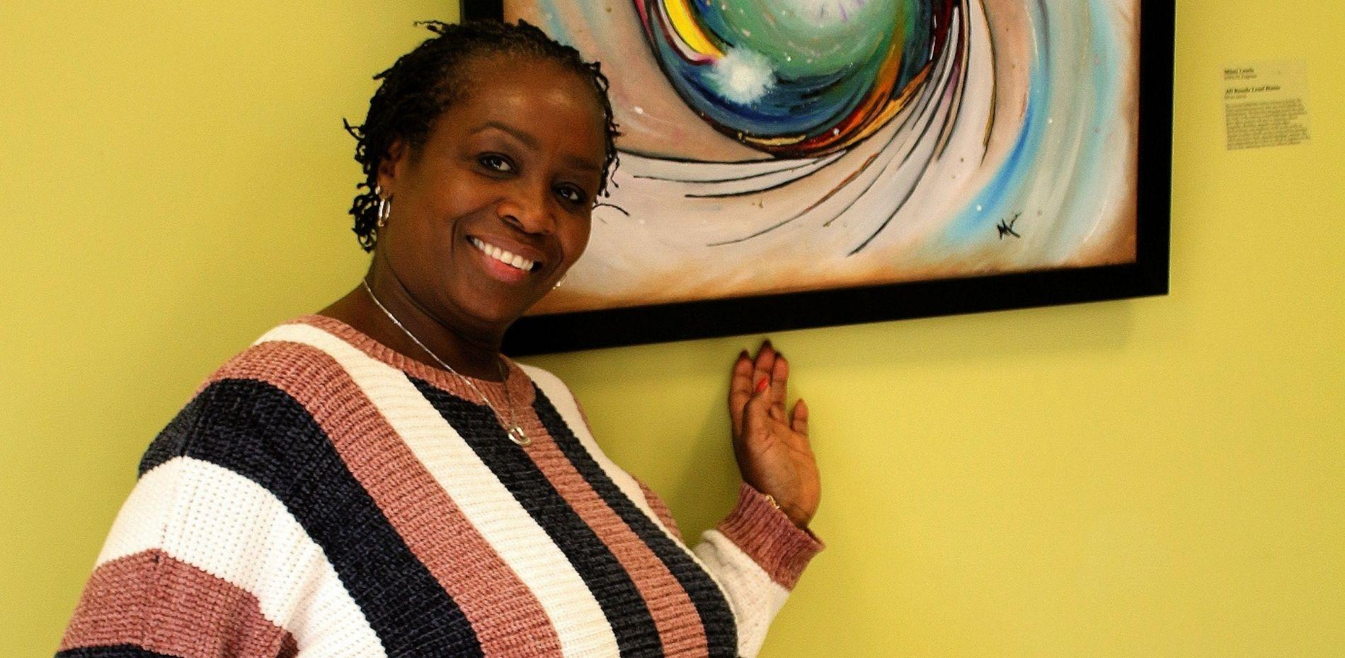 "Mimi Lewis, academic programs coordinator, stands next to her featured artwork entitled ""All Roads Lead Home."""