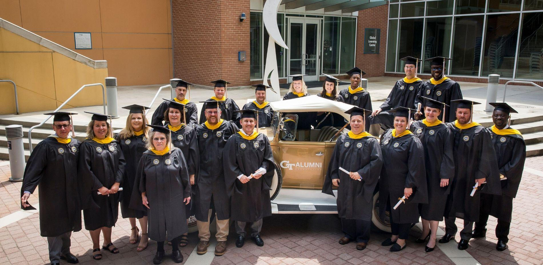 Professional Master's in Occupational Safety and Health graduates stand in front of the Ramblin' Wreck in their caps and gowns.