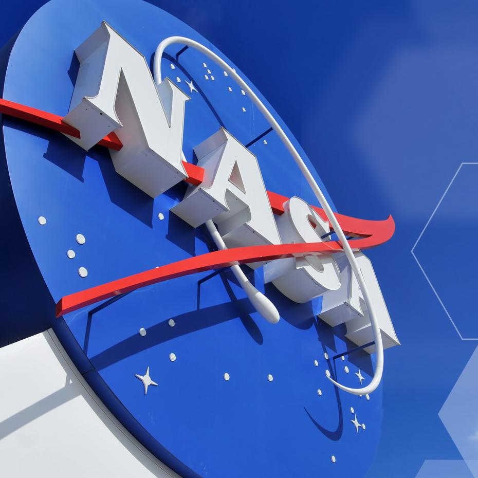 NASA logo, as part of a white building, against a blue sky.