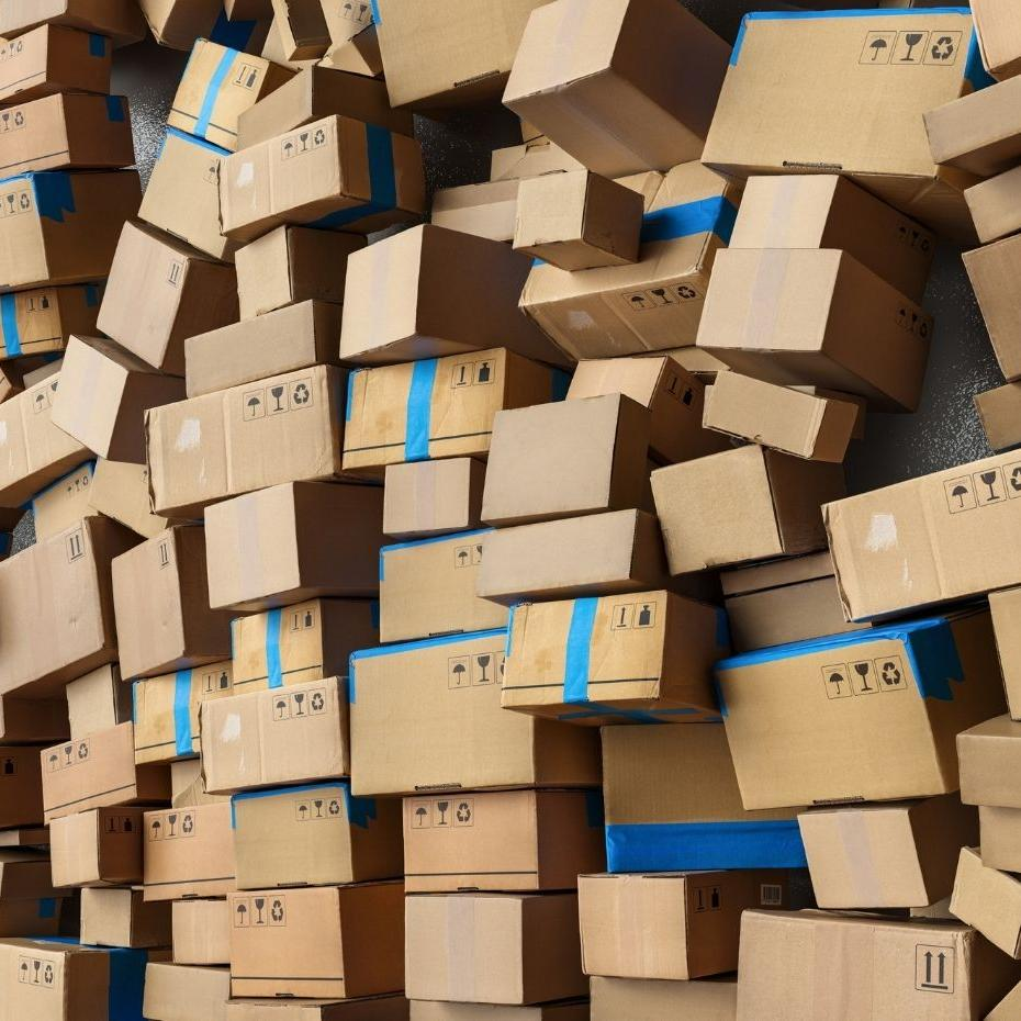 Many stacked cardboard shipping boxes in logistics warehouse before moving to delivery.